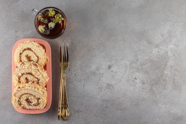 Plakje broodje cake en kopje thee op stenen achtergrond.