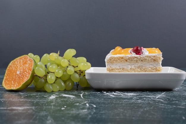 Plakje cake, druiven en sinaasappel op blauwe muur.
