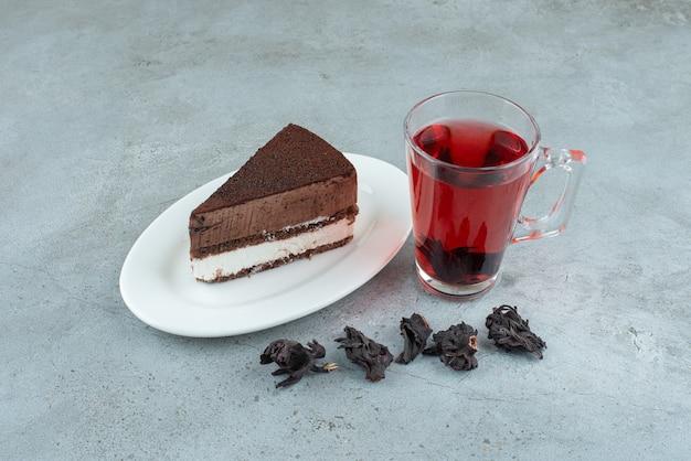 Plakje cake en glas thee op marmeren oppervlak. hoge kwaliteit foto