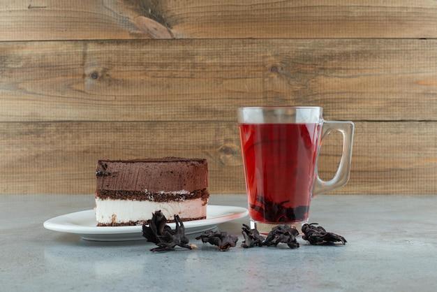 Plakje cake en glas thee op marmeren tafel.