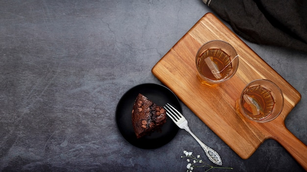 Plakje cake en thee kopjes op een houten steun op een grijze achtergrond