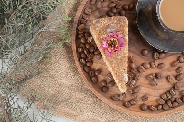 Plakje cake, koffie en koffiebonen op houten plaat