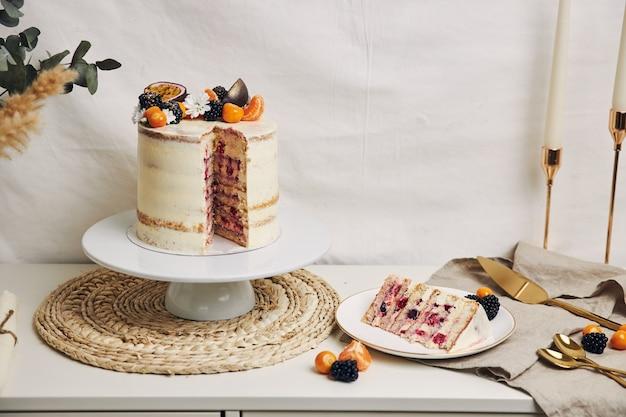 Plakje cake met bessen en passievruchten op tafel achter een witte achtergrond