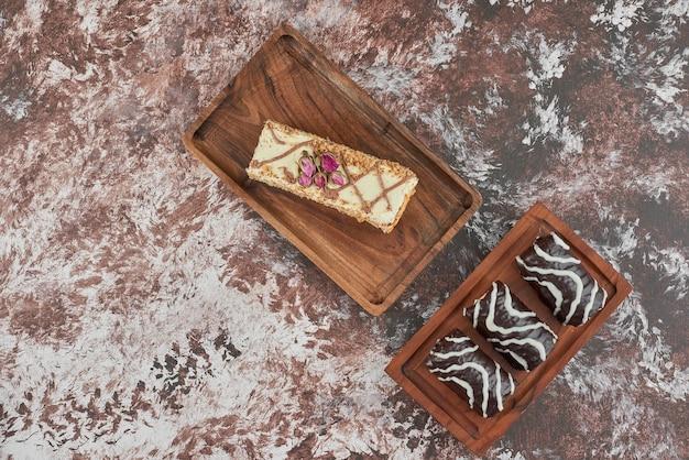 Plakje cake met brownies op een houten bord.