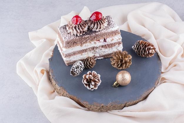 Plakje cake met kerst ornamenten op houten stuk.