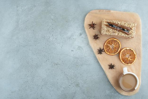 Plakje cake met stukjes sinaasappel en koffie op een houten bord. hoge kwaliteit foto