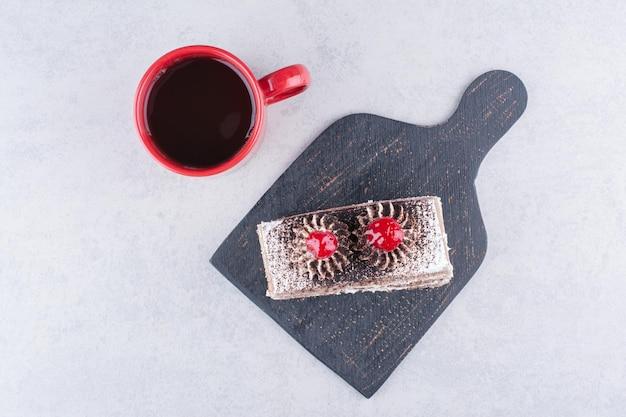 Plakje cake op donkere bord met kopje thee.