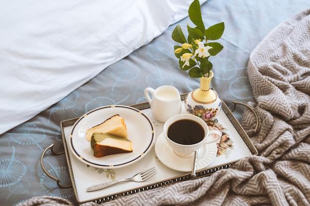 Plakje cheesecake met een kopje koffie en bloem in een lade