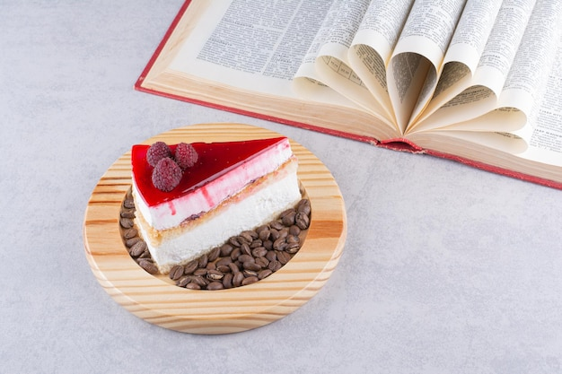 Plakje cheesecake met koffiebonen en boek.