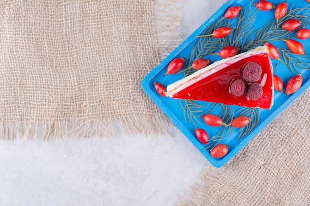 Plakje cheesecake met verse rozebottels op blauw bord.