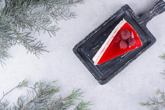 Plakje cheesecake op zwarte bord met pijnboomtak.