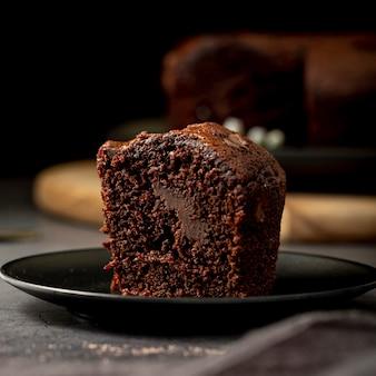 Plakje chocoladecake op een zwarte plaat