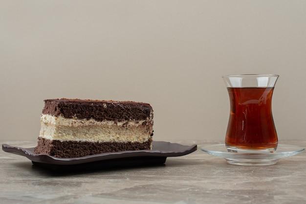 Plakje chocoladetaart en glas thee op marmeren tafel.
