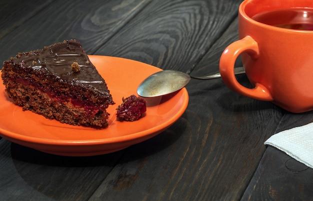 Plakje chocoladetaart in een bord en mok thee op een vintage tafel tijdens het ontbijt