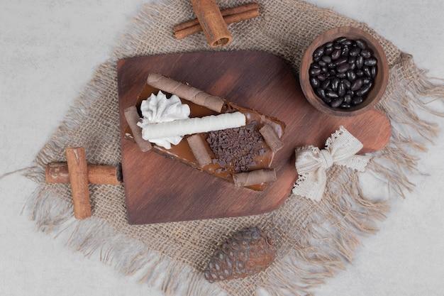 Plakje chocoladetaart, kaneel en dennenappel op jute. hoge kwaliteit foto