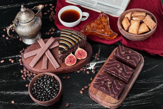 Plakje chocoladetaart met koekjes en thee.