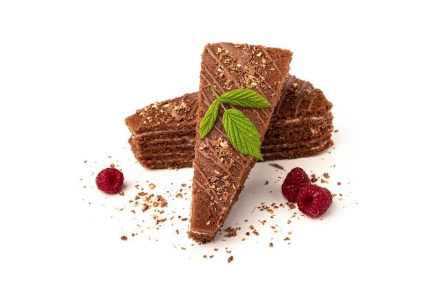 Plakje chocoladetaart met melkvulling en framboos geïsoleerd op wit.