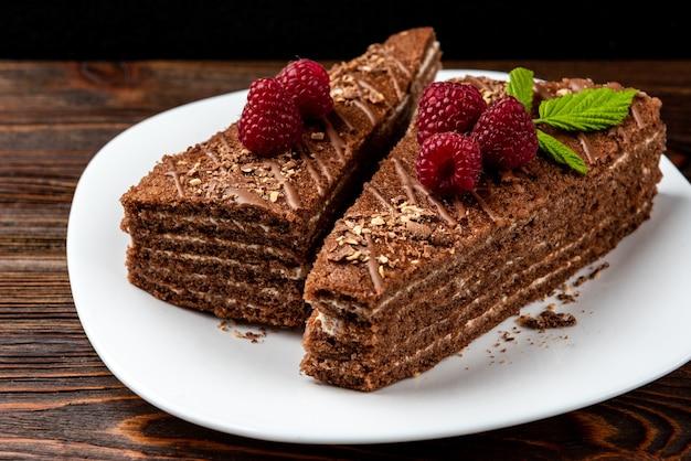 Plakje chocoladetaart met melkvulling en framboos op witte plaat op donkere houten tafel.