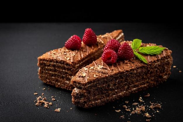 Plakje chocoladetaart met melkvulling en framboos op zwarte ondergrond.