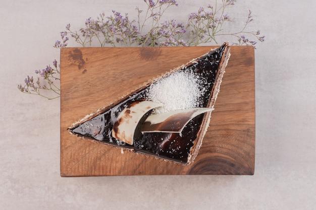 Plakje chocoladetaart op een houten bord.