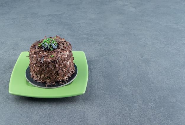 Plakje chocoladetaart op groene plaat.