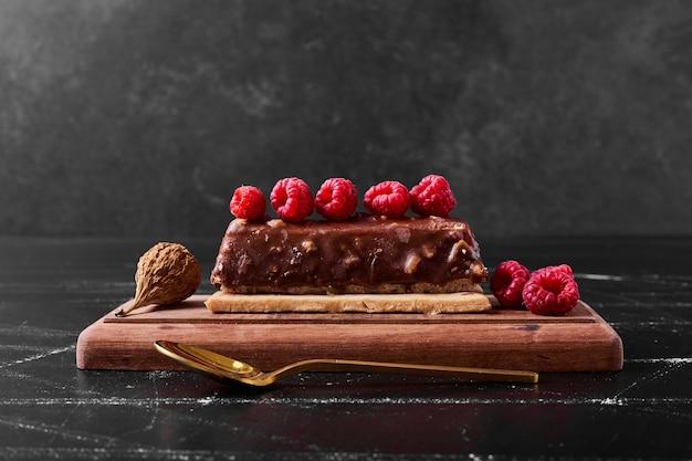 Plakje chocoladetaart op houten schotel.