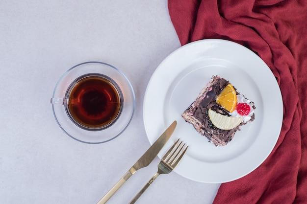Plakje chocoladetaart op witte plaat met kopje thee.