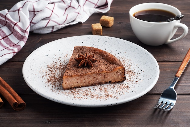 Plakje chocolate curd casserole op een bord, een gedeelte fluitje van een cent met chocolade en koffie. donkere houten rustieke achtergrond.