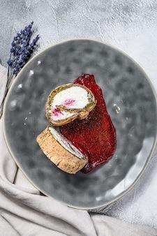 Plakje dessertbroodje met aardbeienjam en room