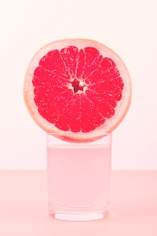 Plakje grapefruit over het glas tegen roze achtergrond