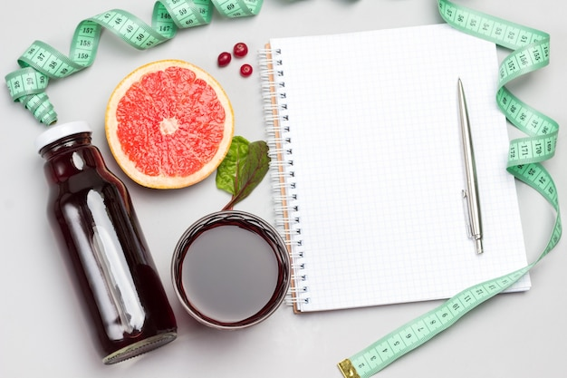 Plakje grapefruit, veenbessen, sap in glas en in fles, meetlint. plat leggen.