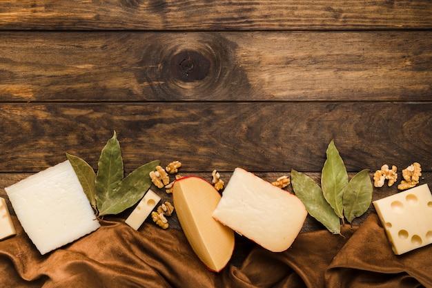 Plakje kaas; laurierbladeren en walnoot schikken onderaan de houten achtergrond met zijde materiaal textiel