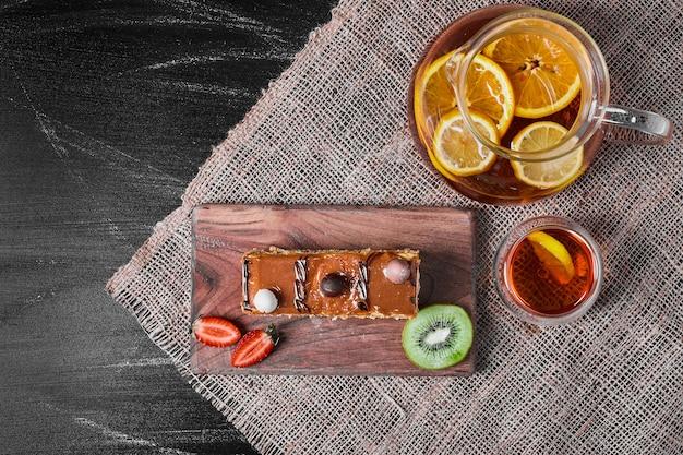 Plakje karameltaart met limonade op een houten schotel.