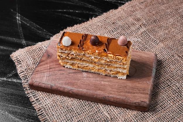 Plakje karameltaart op een houten schotel.