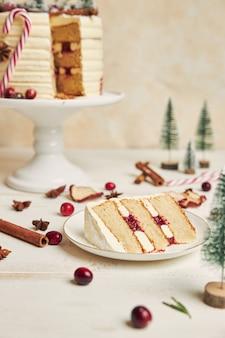 Plakje koekje met laagjes room op een bord en een cake erachter