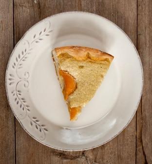 Plakje open perzik-abrikozentaart op witte plaat op houten tafelblad weergave plat lag