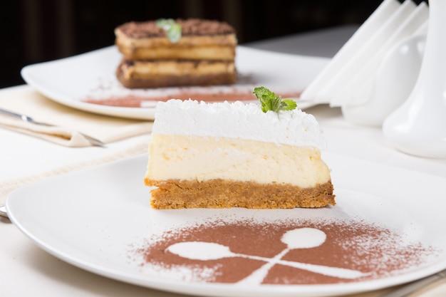 Plakje pittige citroen cheesecake gegarneerd met room op een koekjesbodem geserveerd aan tafel met de contouren van twee gekruiste lepels in chocoladepoeder ernaast