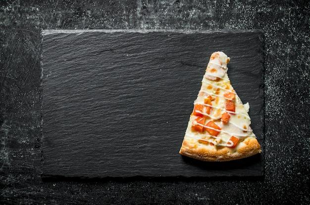 Plakje pizza met kip, tomaten en kaassaus op rustieke tafel