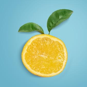 Plakje sinaasappel met bladeren op blauw. bovenaanzicht.