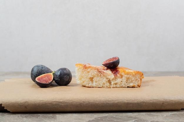 Plakje taart en verse vijgen op een houten bord.