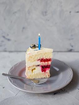 Plakje verjaardagstaart met een aangestoken kaars en vork op een grijze achtergrond. meisjescake, bakkerij- en kookconcept