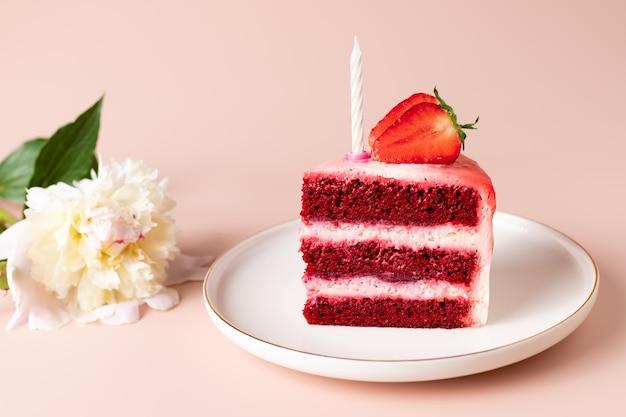 Plakje verjaardagstaart met kaars en pioenroos bloemen rood fluwelen cake met bessen