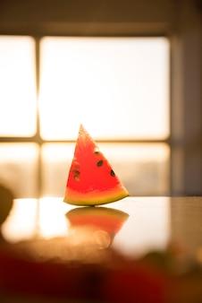 Plakje watermeloen op het bureau tegen het venster vervagen
