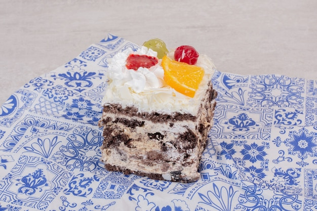Plakje witte cake met fruitplakken op tafellaken.