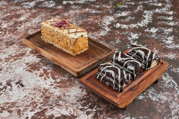 Plakje worteltaart met brownies op een houten bord.