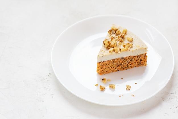Plakje worteltaart met kokosroom en walnoten op een wit bord rauw dessert geen gebakken goederen