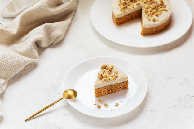 Plakje worteltaart met kokosroom en walnoten op een witte plaat rauwe cake geen gebakken goederen