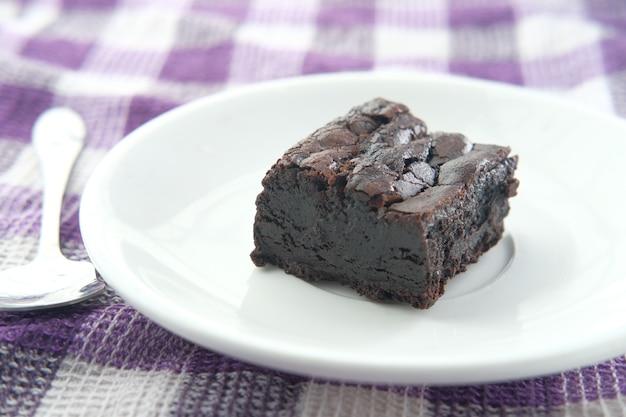 Plakje zelfgemaakte brownie op plaat op tafel