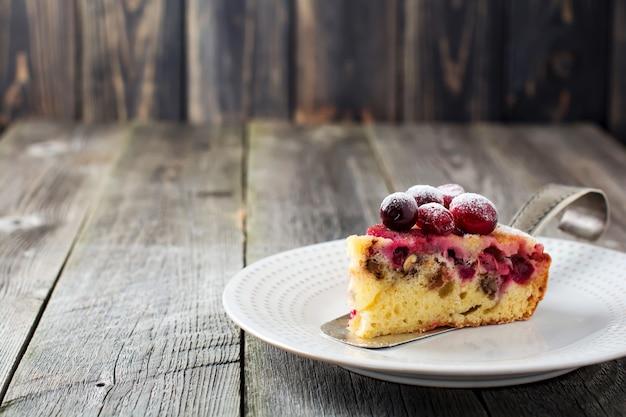 Plakje zelfgemaakte cranberry cake met walnouts, bessen en poedersuiker op een keramische plaat. ruimte voor tekst. rustieke stijl. selectieve aandacht.