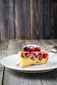 Plakje zelfgemaakte cranberrycake met walnoten, bessen en poedersuiker op een keramische plaat